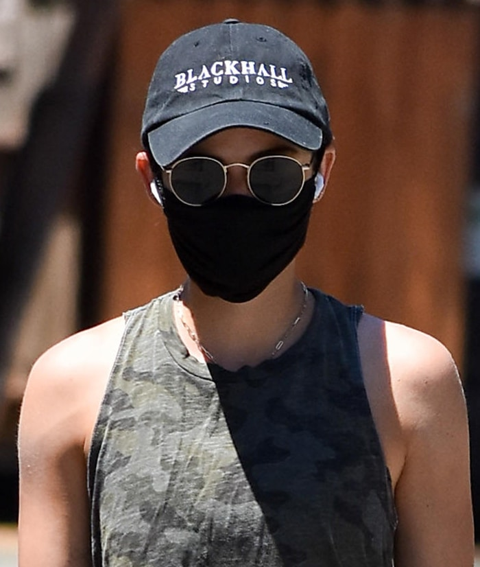 Lucy Hale keeps a low-key look with black face mask, cap, and sunglasses