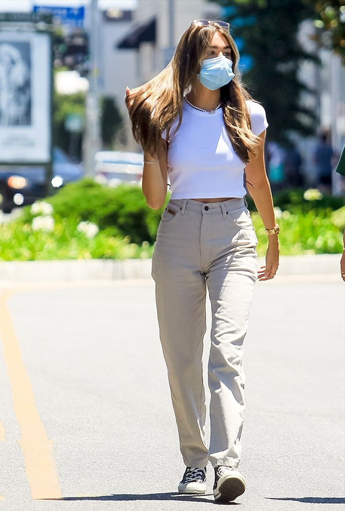 Madison Beer shows off her slender figure in white crop top and high-waisted beige jeans