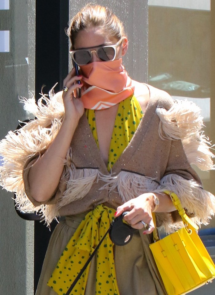 Olivia Palermo wears a pair of square sunglasses and wraps a Le Scarf No.14 scarf around her face