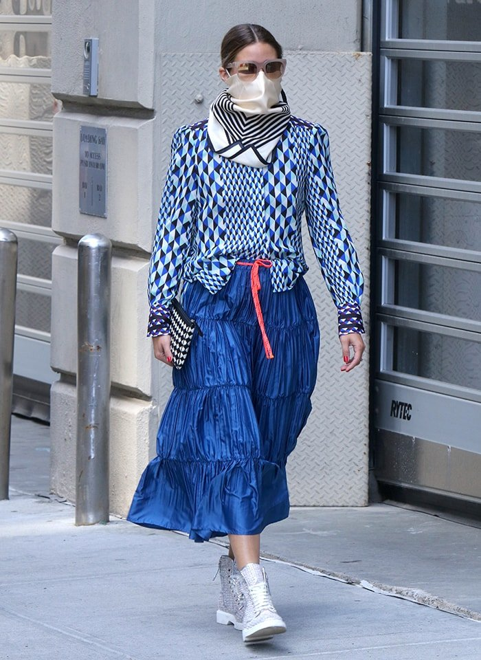 Olivia Palermo continues her style streak in a patterned, blue long-sleeved blouse and a pleated, ruffled midi skirt