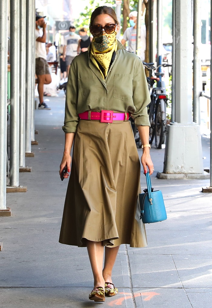 Olivia Palermo wears an earth-tone midi skirt and a loose shirt with a hot pink belt and yellow scarf