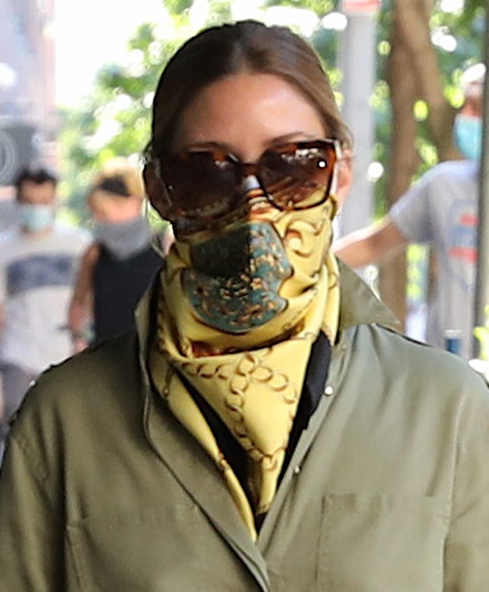 Olivia Palermo stays safe in style with a yellow silk scarf covering her face mask