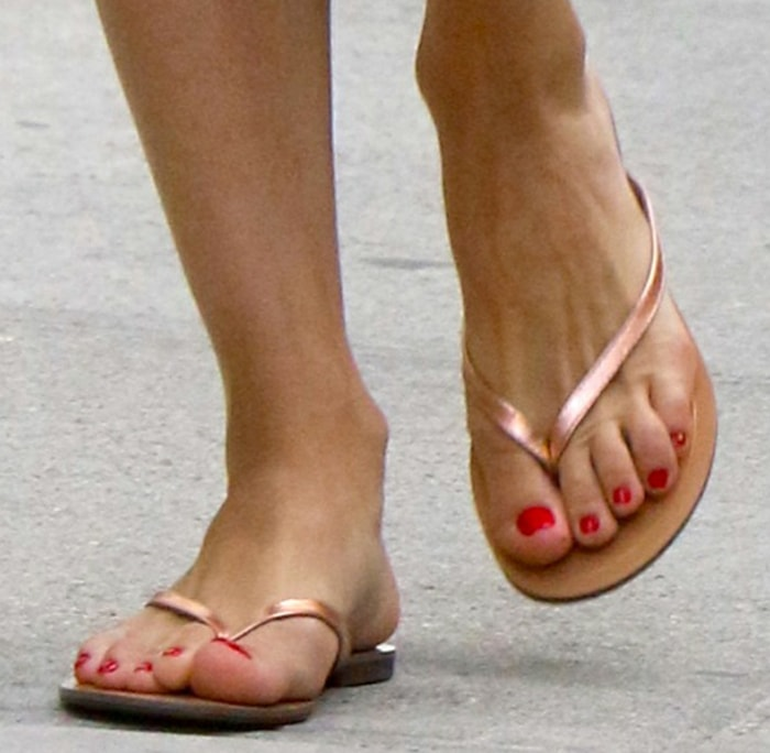 Olivia Palermo shows off her feet in Tkees flip flops as she dries up her newly pedicured toes