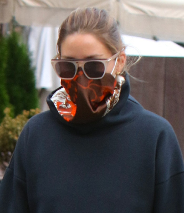 Olivia Palermo wears a red scarf as a face mask to slow down the spread of the novel coronavirus