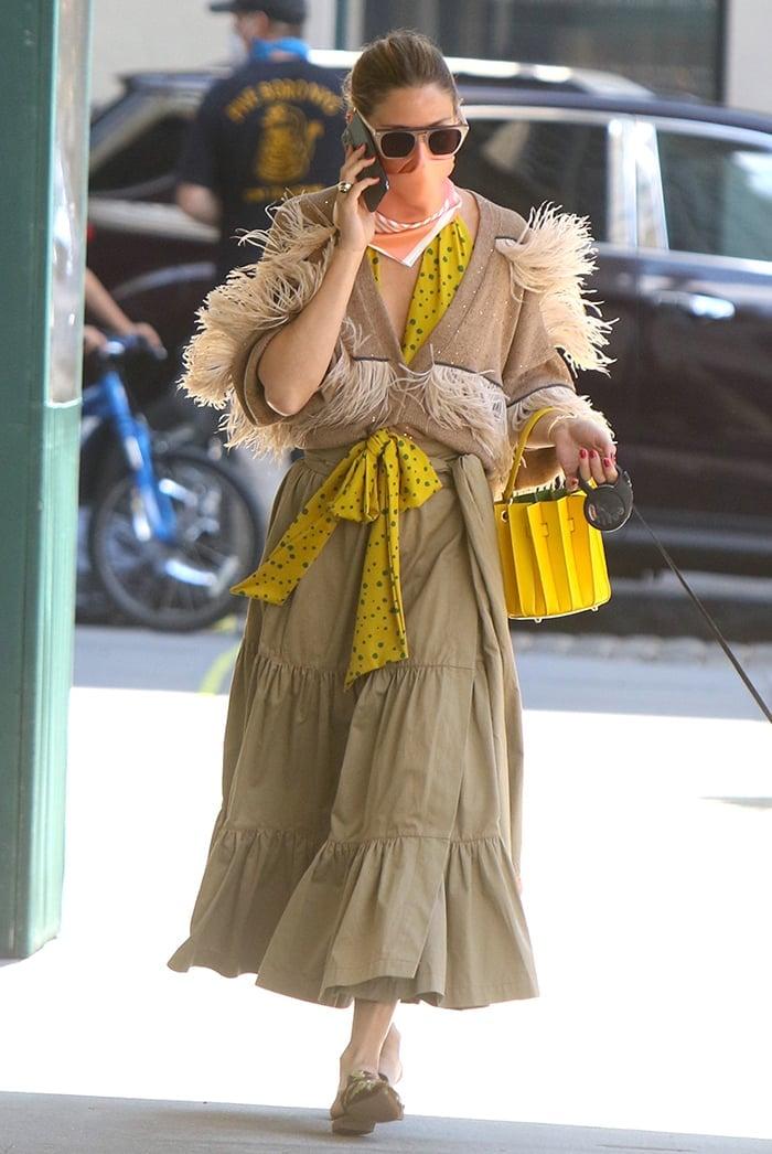 Olivia Palermo wears a khaki green tiered midi skirt with a yellow polka-dot blouse