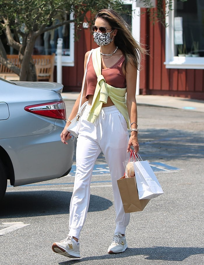 Alessandra Ambrosio shows off her toned midriff in a crop tank top and white sweatpants