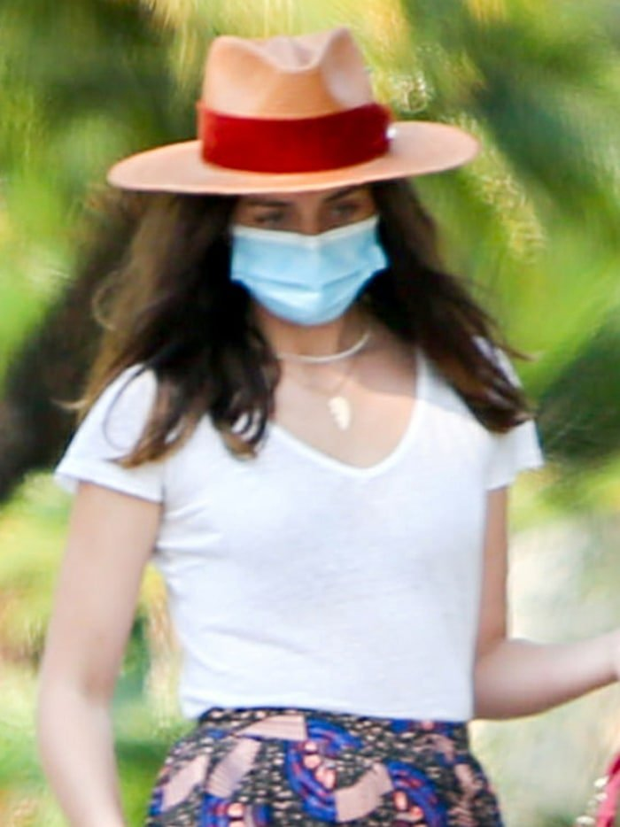 Ana de Armas styles her look with a Panama hat with a red velvet ribbon