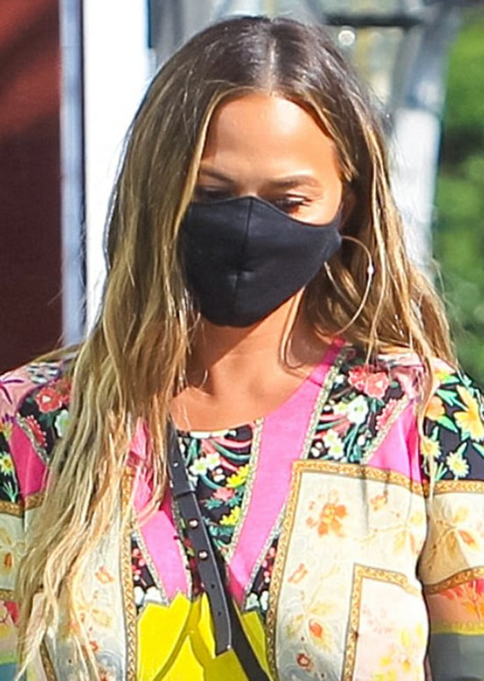 Chrissy Teigen wears a face mask and lets her long tresses down