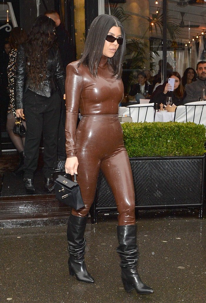 Kourtney Kardashian in Balmain brown latex suit at L'Avenue Restaurant in Paris, France on March 1, 2020