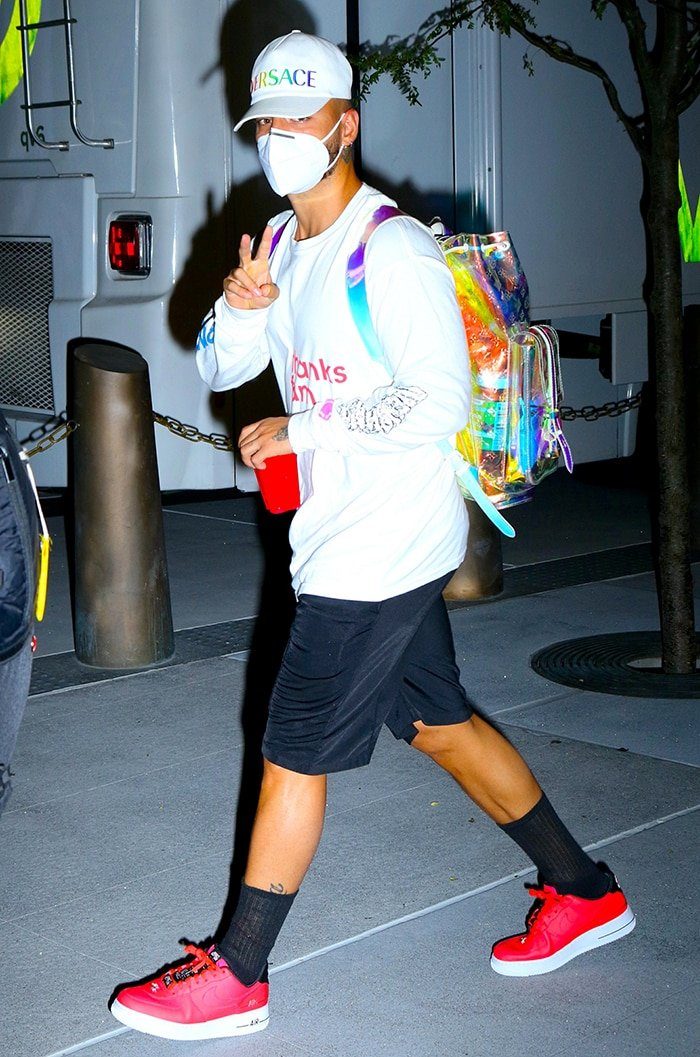Colombian singer Maluma wears red Nike Air Force 1 and carries a holographic Louis Vuitton backpack