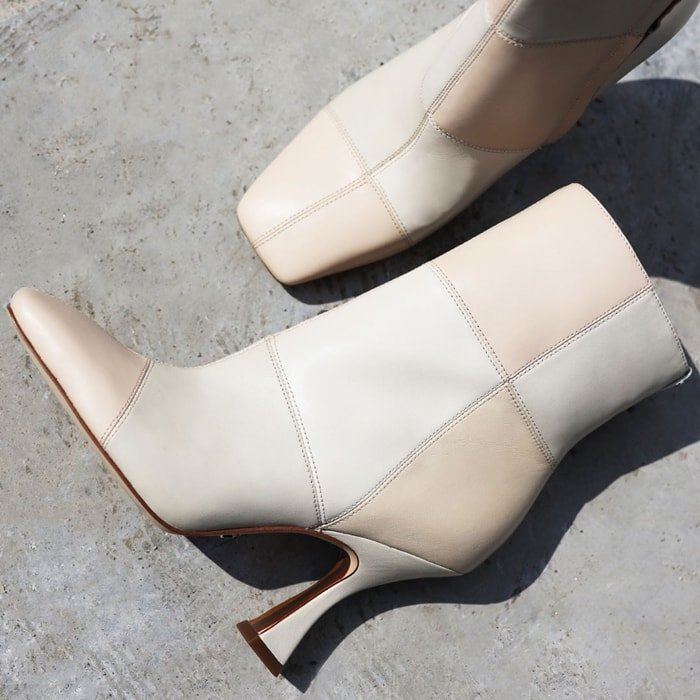 These ivory/grey/nude leather boots feature a tonal patchwork upper, curvy, sculpted heel and tapered square toe