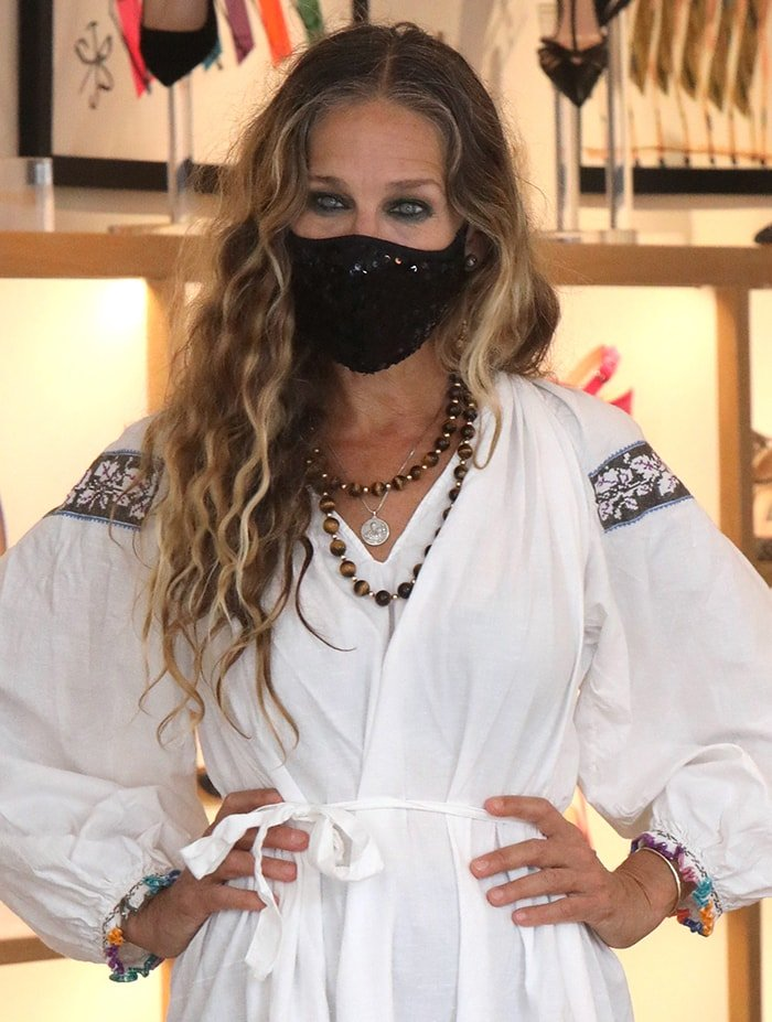 Sarah Jessica Parker wears a bead necklace and a sequined face mask