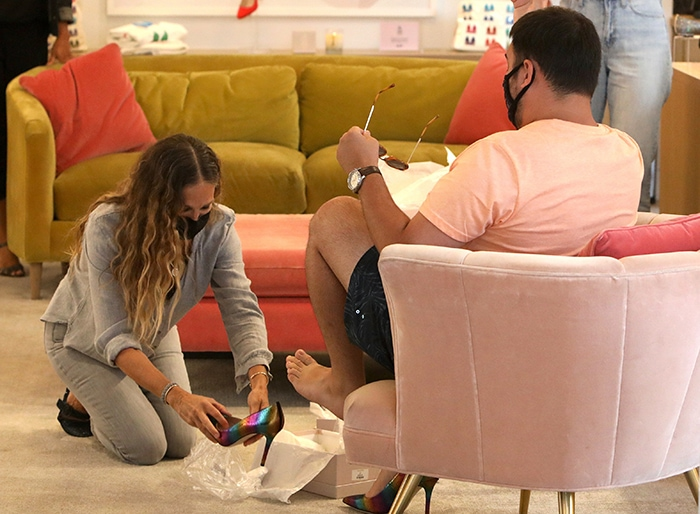 Sarah Jessica Parker on her knees as she helps a customer slide a pair of rainbow pumps on his feet