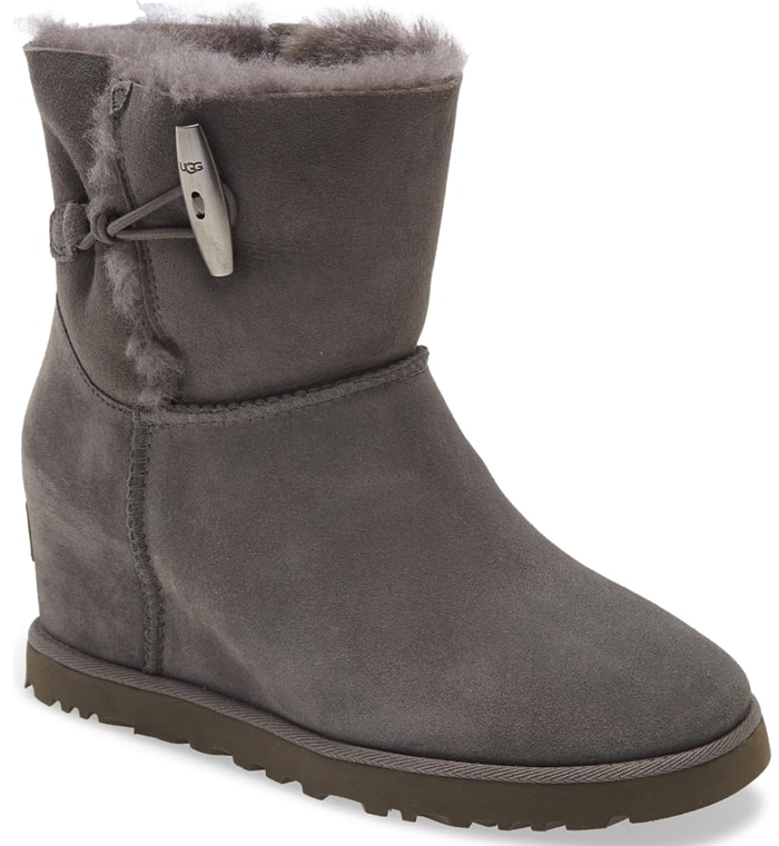 A coyly hidden wedge brings a fashion-forward update to a fan-favorite boot featuring plush genuine shearling at the toggle-cinched split shaft