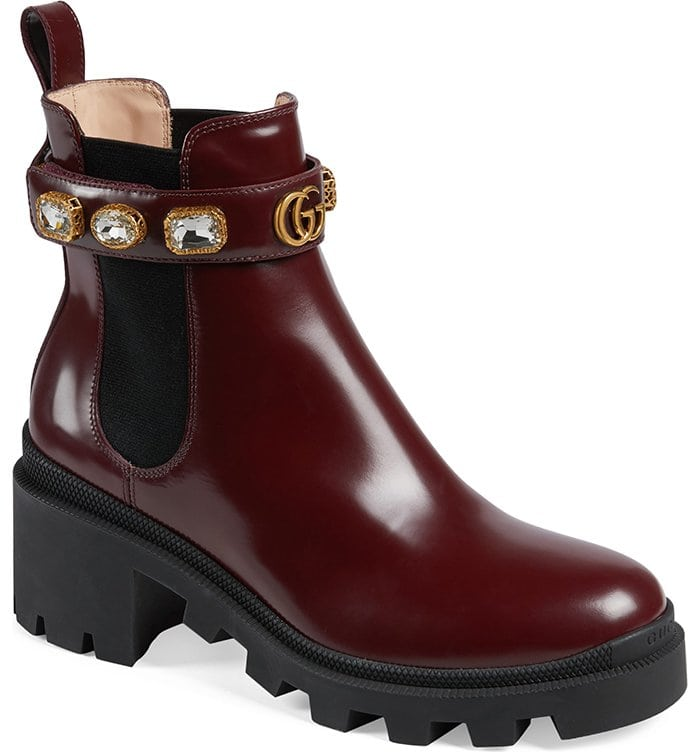 Bejeweled straps encircle the elastic-inset shaft of a sleek leather Chelsea boot set atop a chunky lug sole
