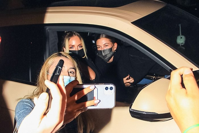 Hailey Bieber and her stylist Maeve Reilly pose for photos with a fan after a dinner date on September 21, 2020