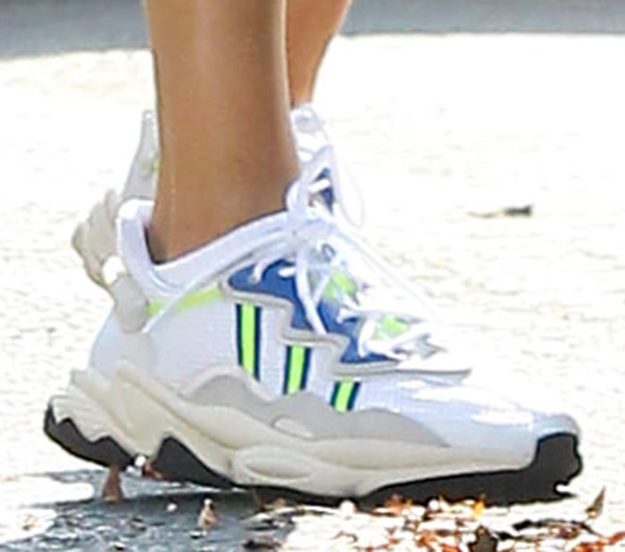 Hailey Bieber completes her look with Adidas Ozweego sneakers in solar yellow and blue colorway