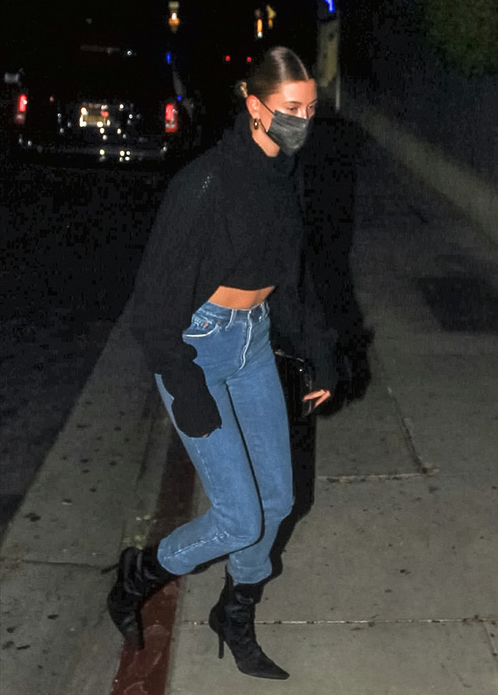 Hailey Bieber flaunts her abs in Y's black knit sweater and Levi's jeans