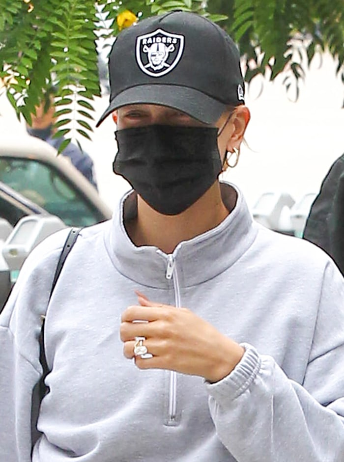 Hailey Bieber keeps a low profile with a baseball cap and a protective face mask