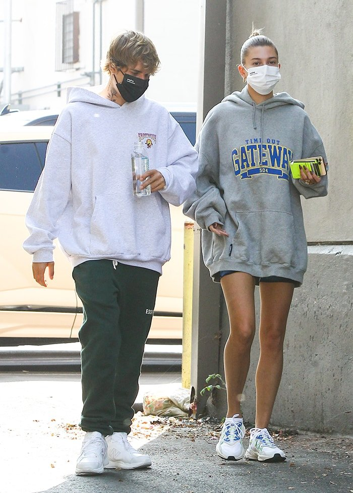 Justin Bieber wears a Saintwoods gray hoodie with Fear of God green sweatpants and white New Balance sneakers