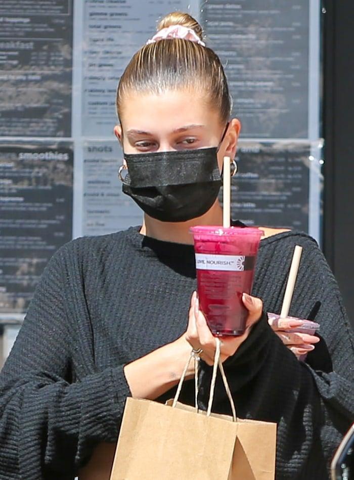 Hailey Bieber wears her hair in a sleek bun with a scrunchie