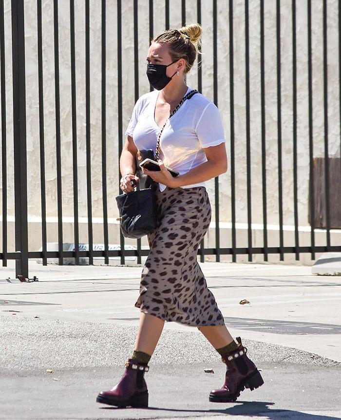 Hilary Duff teams a classic white tee with a leopard-print midi skirt