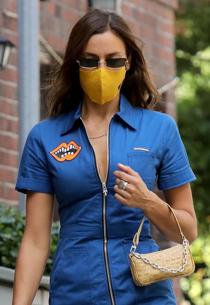 Irina Shayk styles her look with a Sanitation Nation yellow face mask, Linda Farrow sunnies, and By Far mini bag