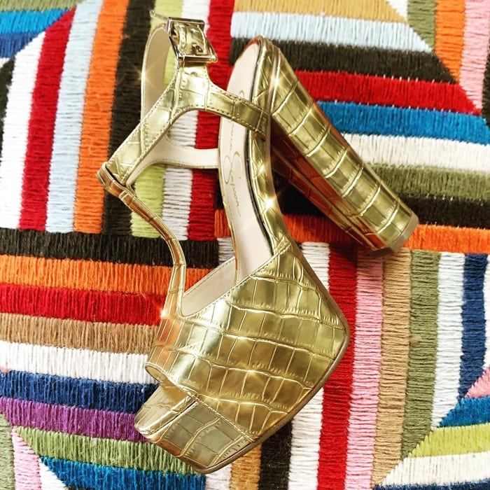 A croc-embossed finish adds textural edge to a gold T-strap sandal set on a lofty platform