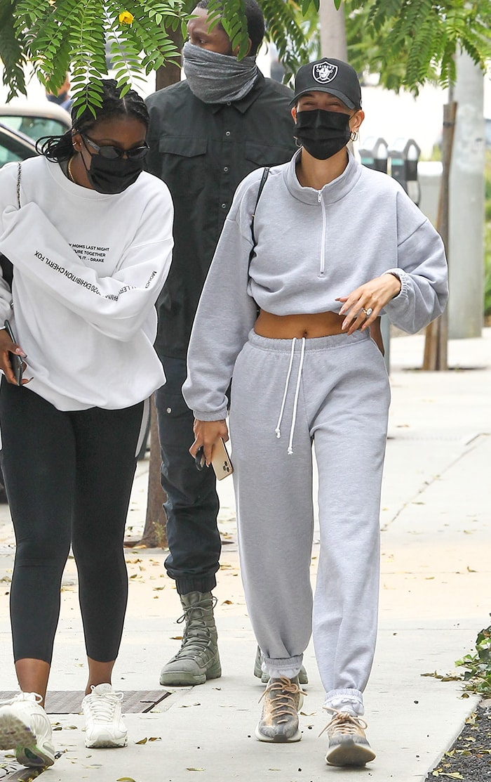Hailey Bieber flashes her abs in gray cropped pullover and matching pants