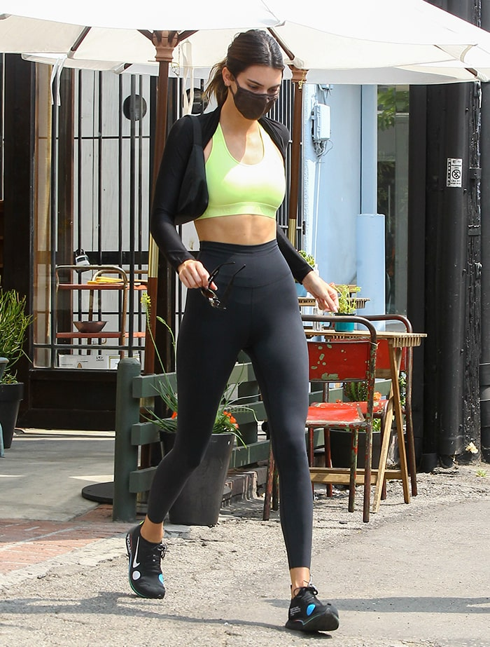 Kendall Jenner shows off her slender curves in green Adidas sports bra and Nike tights