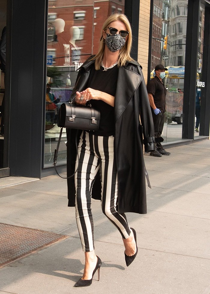 Nicky Hilton wears Alice + Olivia striped pants and a trench coat