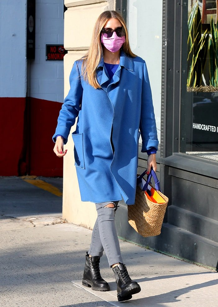 Olivia Palermo does chic layering with a blue coat, a blue top, and a pair of gray skinny jeans