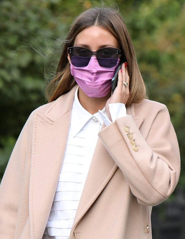 Olivia Palermo keeps a low profile with oversized sunglasses and purple face mask
