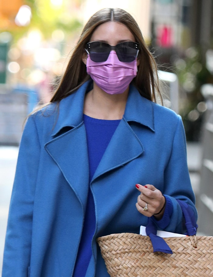 Olivia Palermo styles her glossy tresses straight and wears a lavender face mask with oversized sunglasses