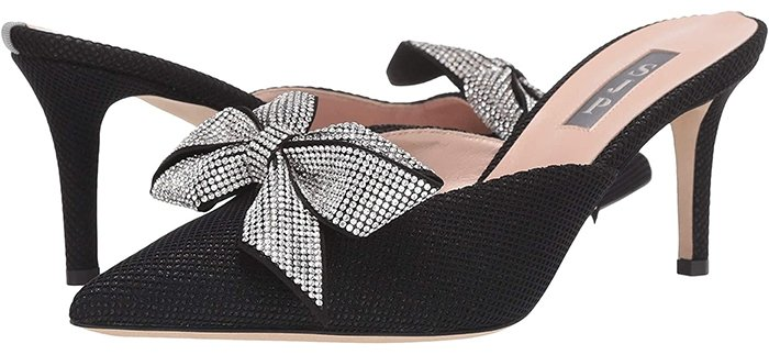 The pointed-toe black slip-on mule is constructed from luxe, shimmery fabric with a bling bow at the flirty V-vamp