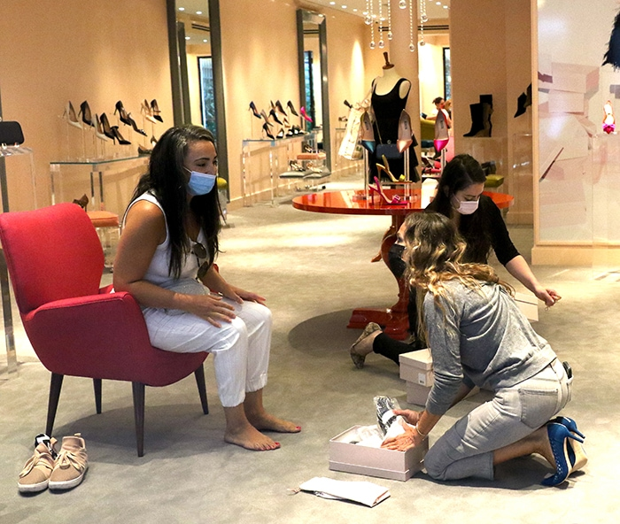 Sarah Jessica Parker helps a customer try a pair of shoes from her collection