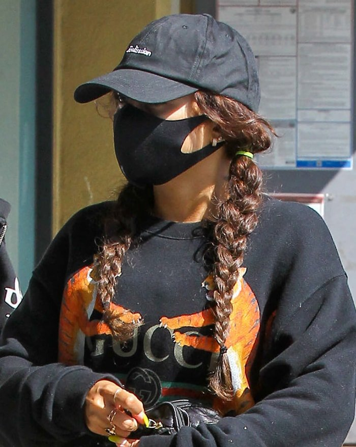 Vanessa Hudgens keeps it low-key with a black cap and face mask