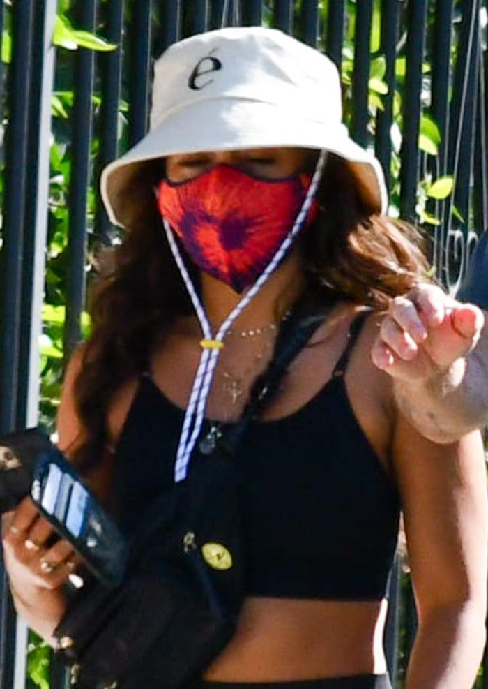 Vanessa Hudgens wears a tie-dye face mask and a bucket hat