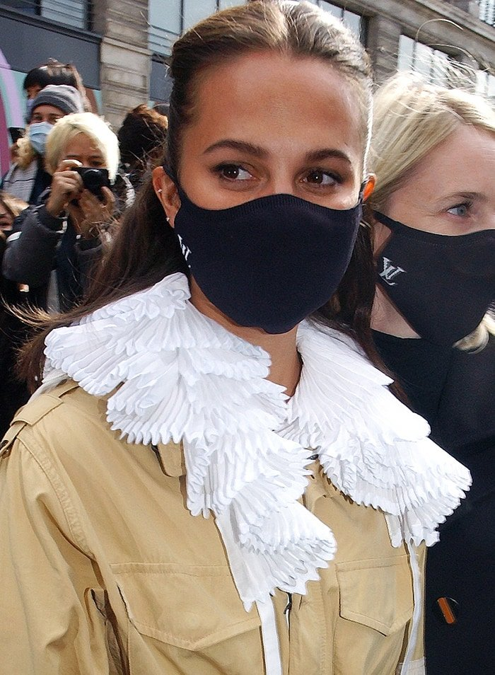 Alicia Vikander wears a Louis Vuitton Resort 2021 utility jacket with white ruffled collar and black face mask