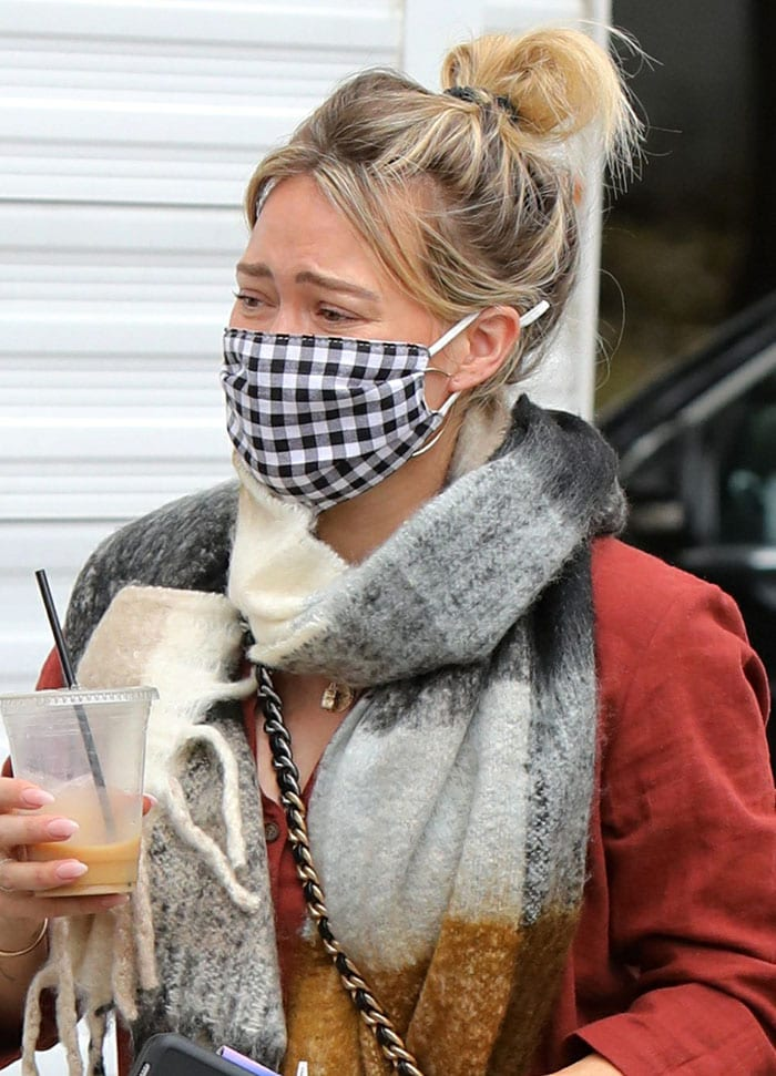 Bare-faced Hilary Duff pulls her hair up into a messy bun