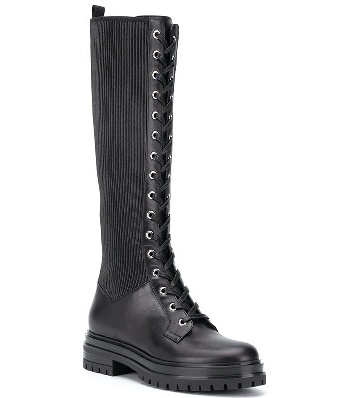 Edgy knee-high combat boots merge a smooth leather construction with rib-knit inserts