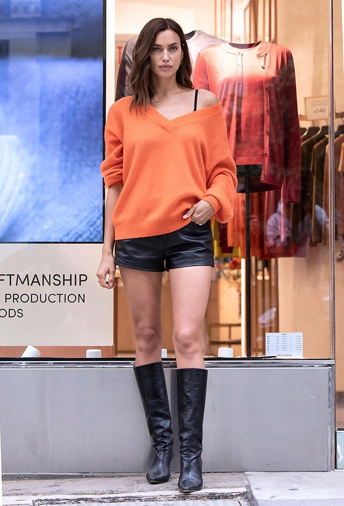 Irina Shayk shows off her long legs in fall-appropriate leather shorts and orange sweater