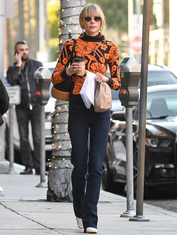 Jaime King wears a vibrant orange flower sweater