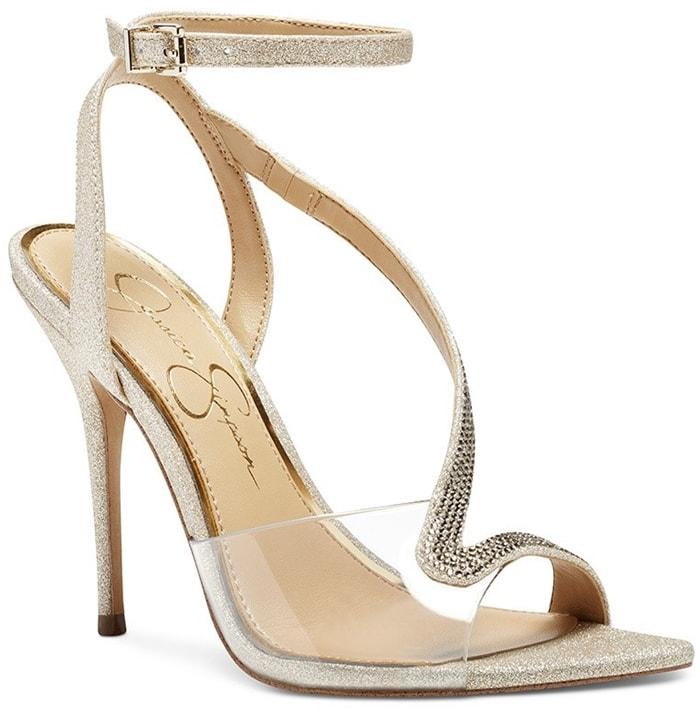 Glittering crystals illuminate the strap of an elegant sandal lifted skyward by a svelte stiletto heel