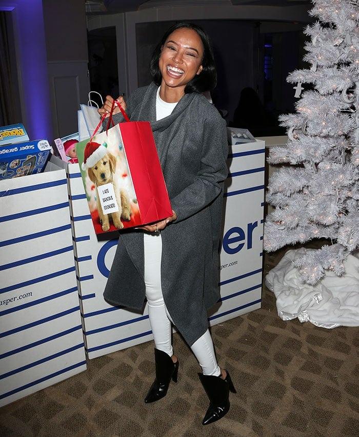 Karrueche Tran poses with a gift bag in a winter white ensemble