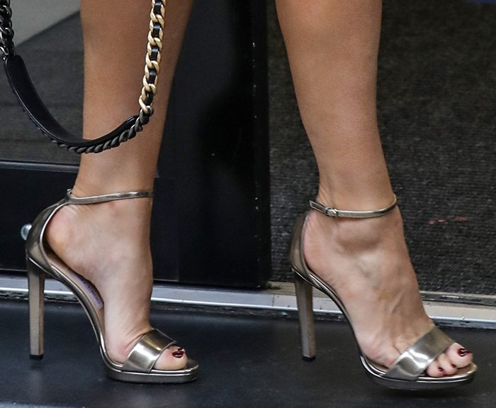 Kelly Brook slips her sexy feet into a pair of gunmetal high heel sandals