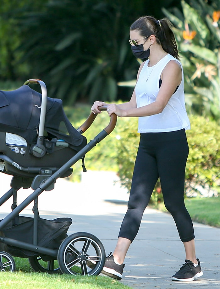 Lea Michele showcases her post-baby body in a white sleeveless top with black leggings