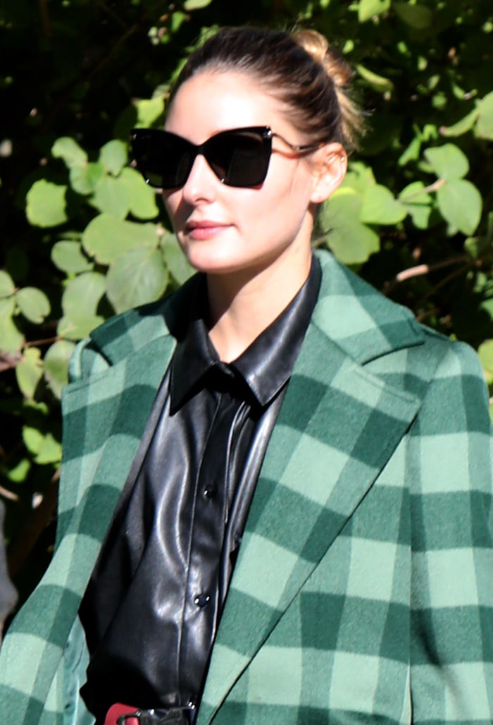 Olivia Palermo wears a bun hairstyle and shields her eyes behind a pair of angular sunglasses