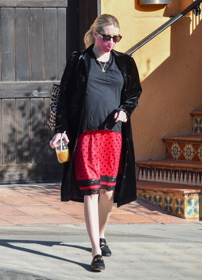 Emma Roberts' maternity look includes a loose tee, a black and red polka dot skirt, and a coat