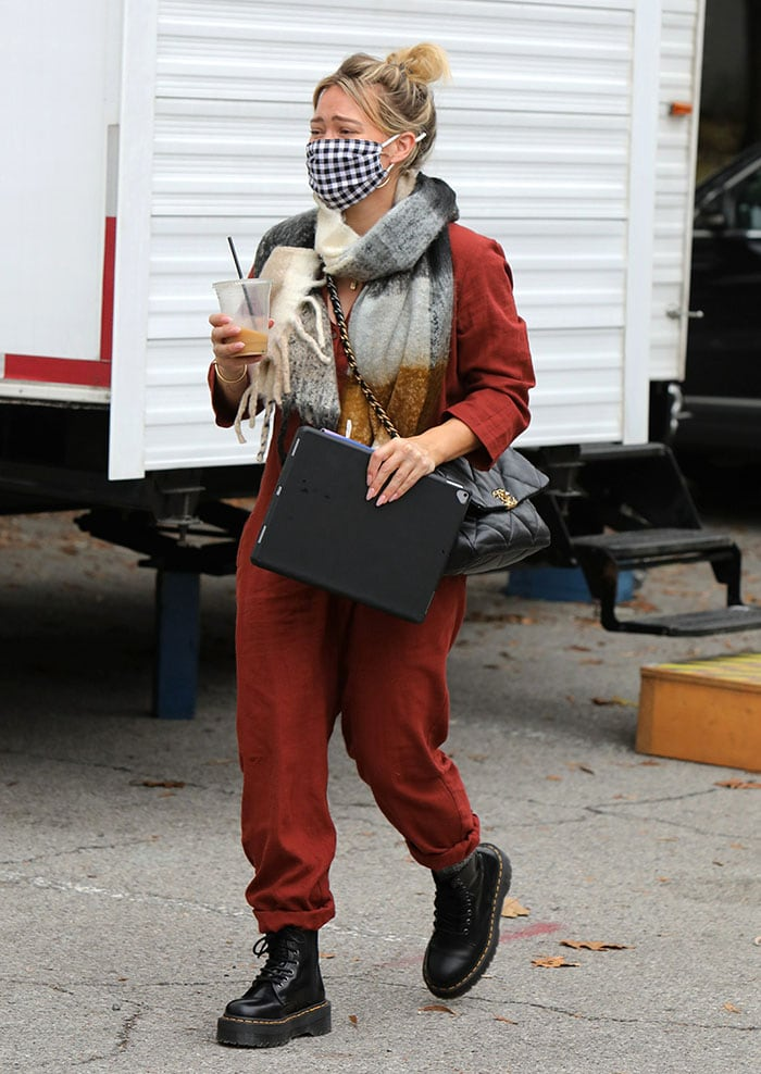 Pregnant Hilary Duff hides her baby bump in a red jumpsuit on the set of Younger in New York City on October 22, 2020